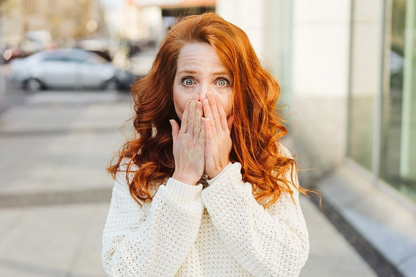 Beautiful red haired woman covering her mouth in fear of showing off her mouth sores. There are two common types of mouth sores that are common: canker sores and cold sores.