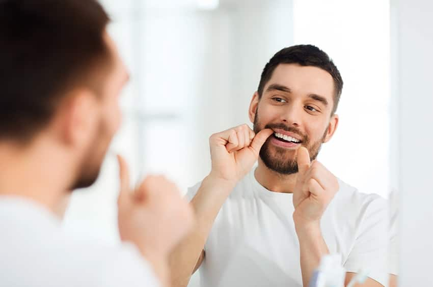 Young man taking the time to floss his teeth. Here are some fun facts about dental floss
