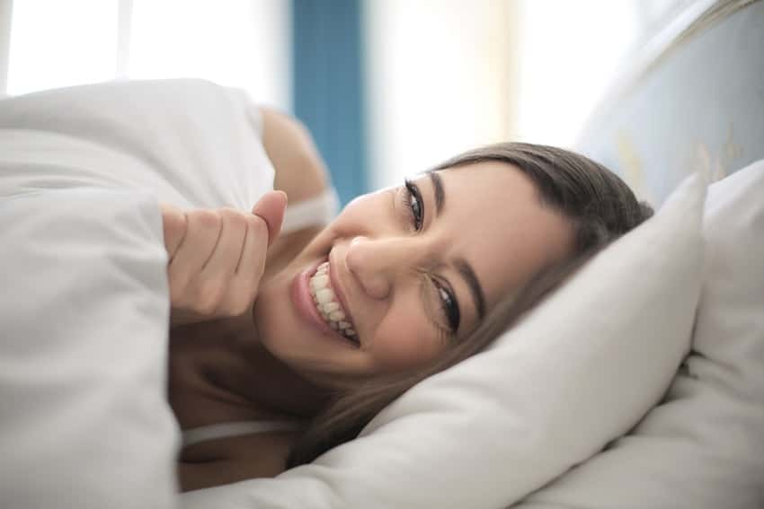 Girl laughing while trying to hide under bed blankets. If your smile could use some brightening, what are you waiting for?