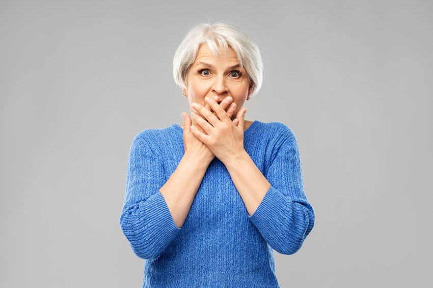 Older woman in blue sweater looks shocked while covering her mouth do to bad breath