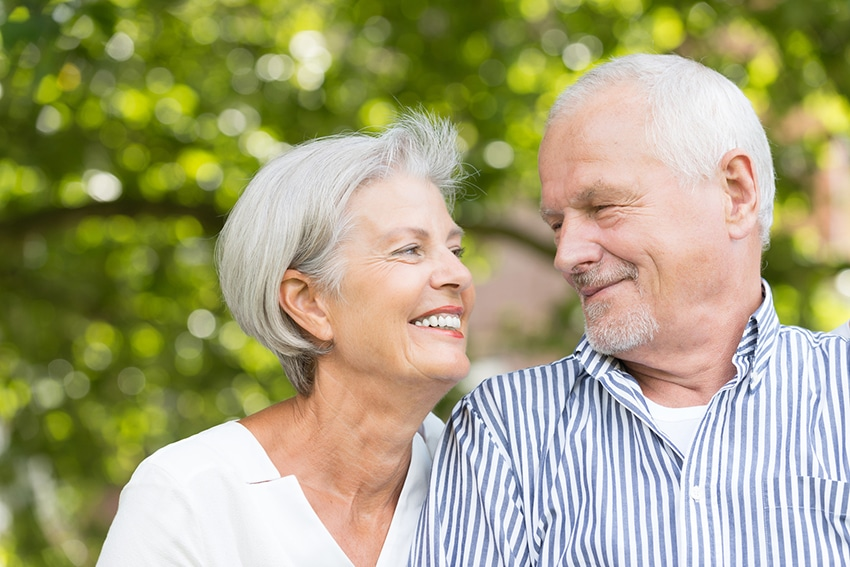 A elderly couple smilng at each other while on a walk
