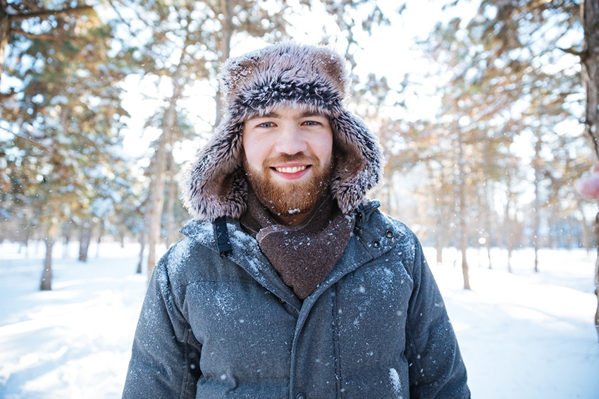 A young man wearing a winter coat and hat while in the snow ou in a forest