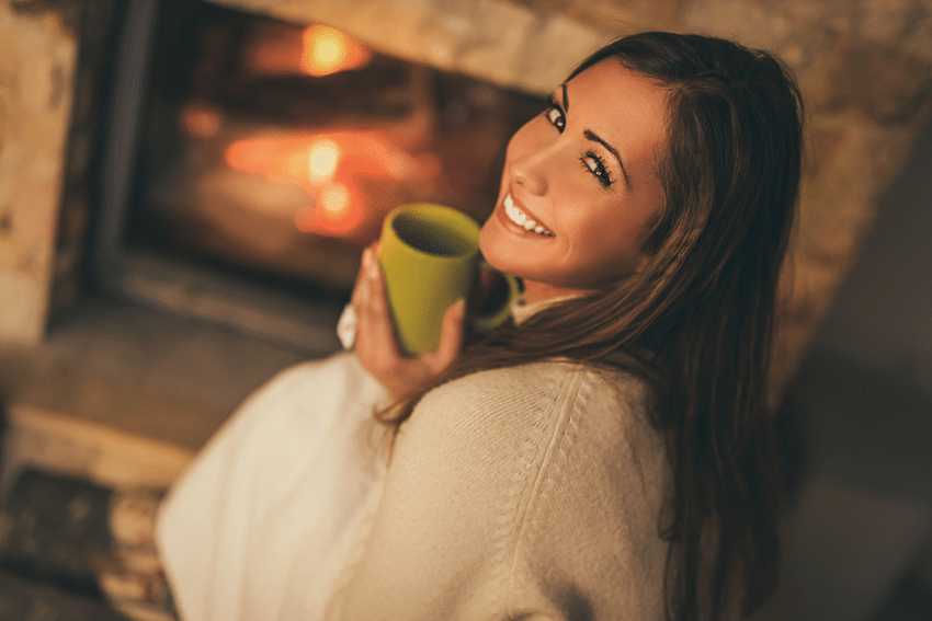A smiling woman sitting by a fire