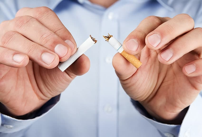 Human hands breaking up cigarette - quit smoking and improve your oral health