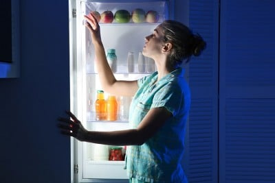 woman looking through the refrigerator late at night