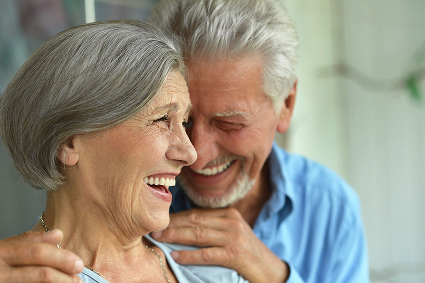 mature couple laugh and embrace while spending time outside