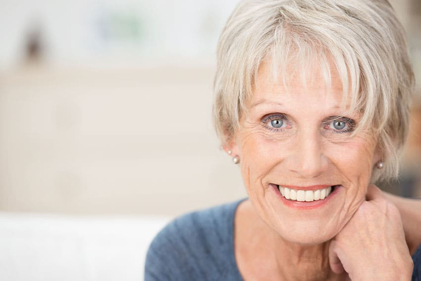 mature woman showing off her new dentures