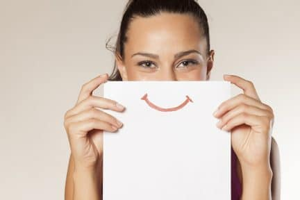 Cute young woman's eyes shine above a piece of paper showing off a big smile