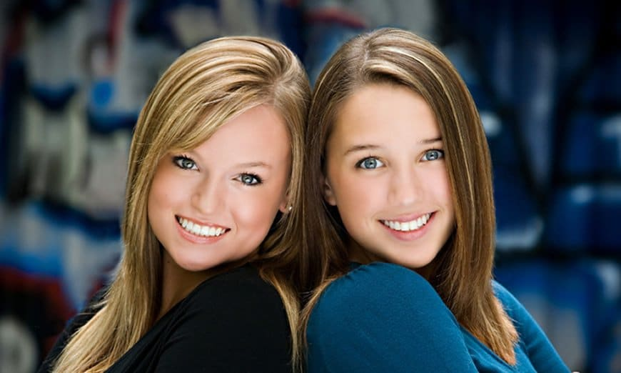 two beautiful young women show off their amazing smiles